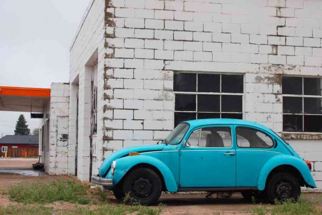 Blue Classic VW Beetle Next to White Brick Wall